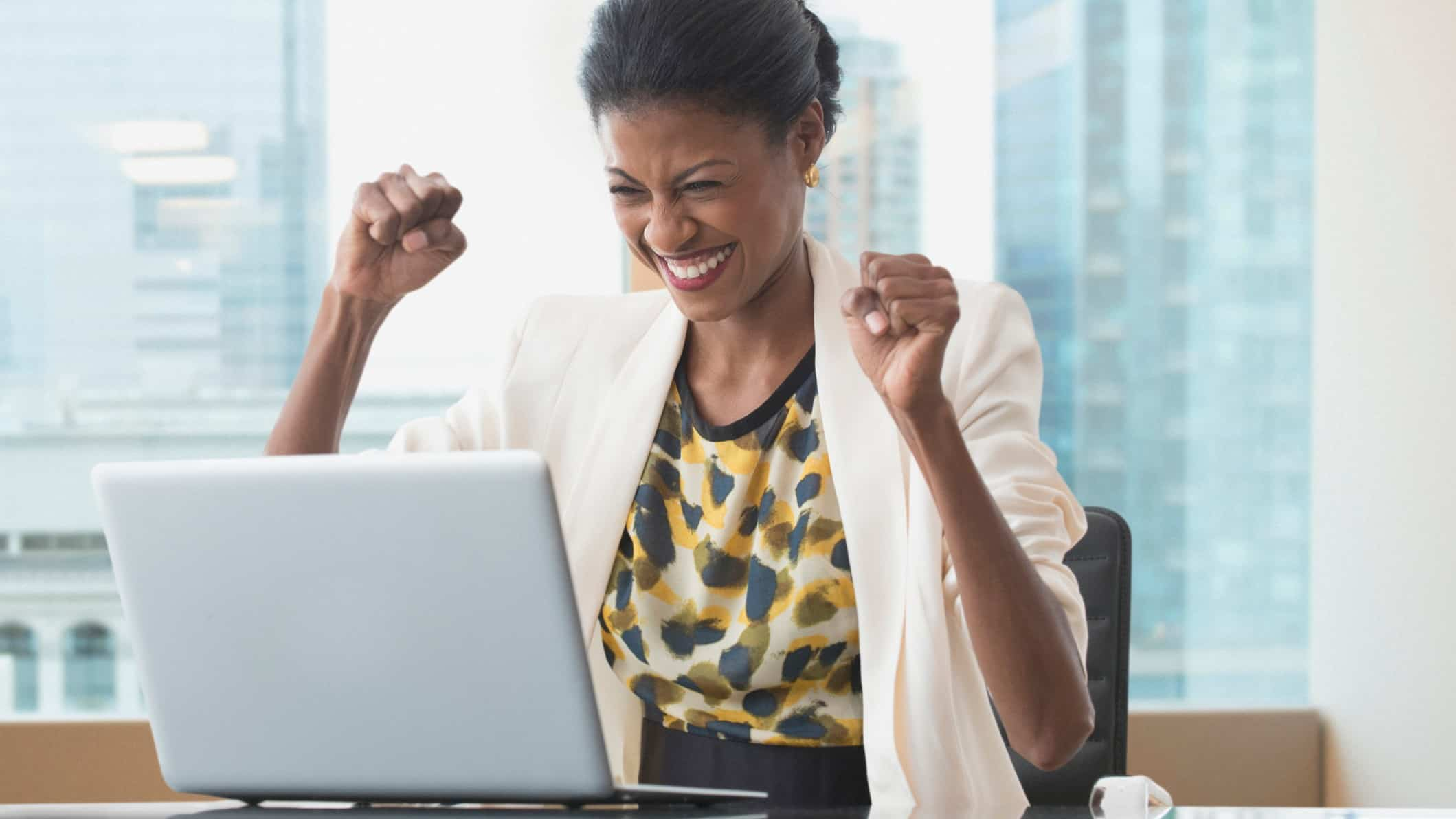 A happy woman at her laptop punches the air, indicating a rising share price