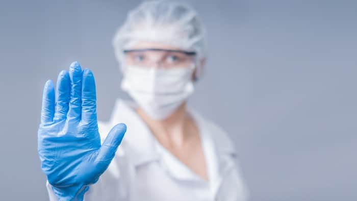 health worker wearing personal protective equipment and gesturing stop with her hands