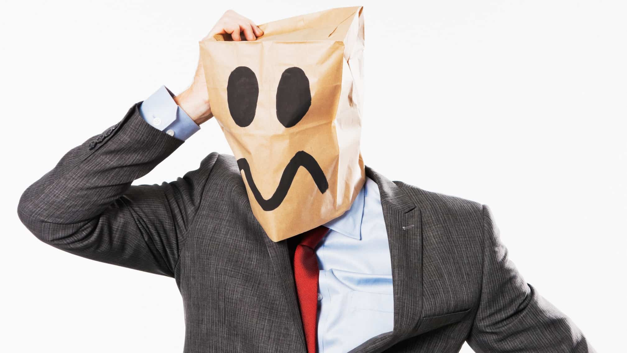 A business man with an idiot face drawn onto a paper bag on his head, indicating a company director using the 'honest idiot'defence