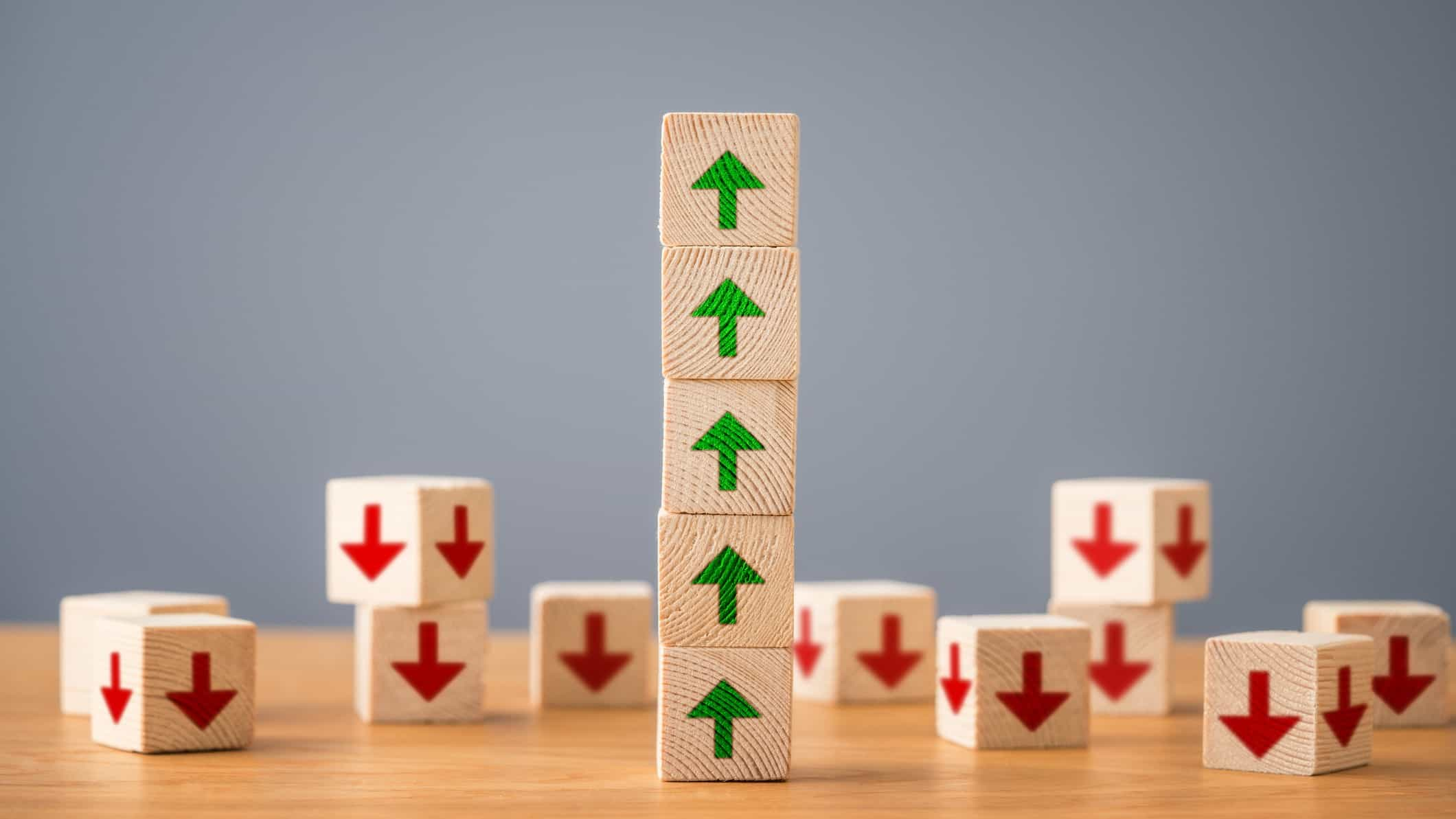 Five stacked building blocks with green arrows, indicating rising inflation or share prices