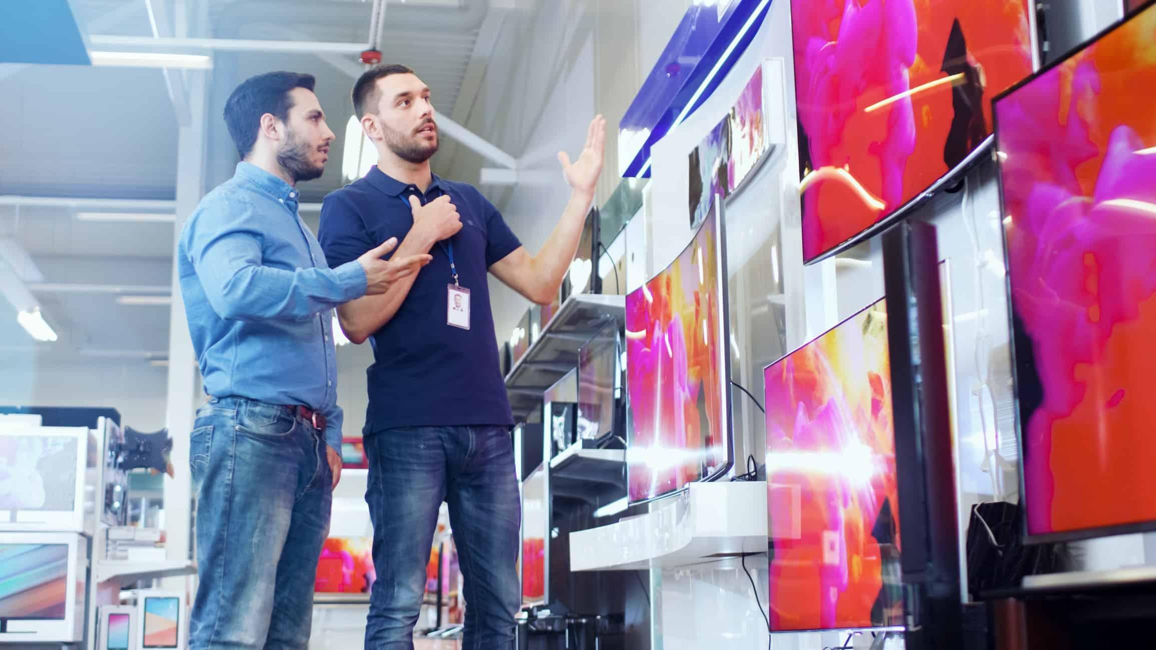 man helping customer looking at tvs in store signifying jb hi-fi share price