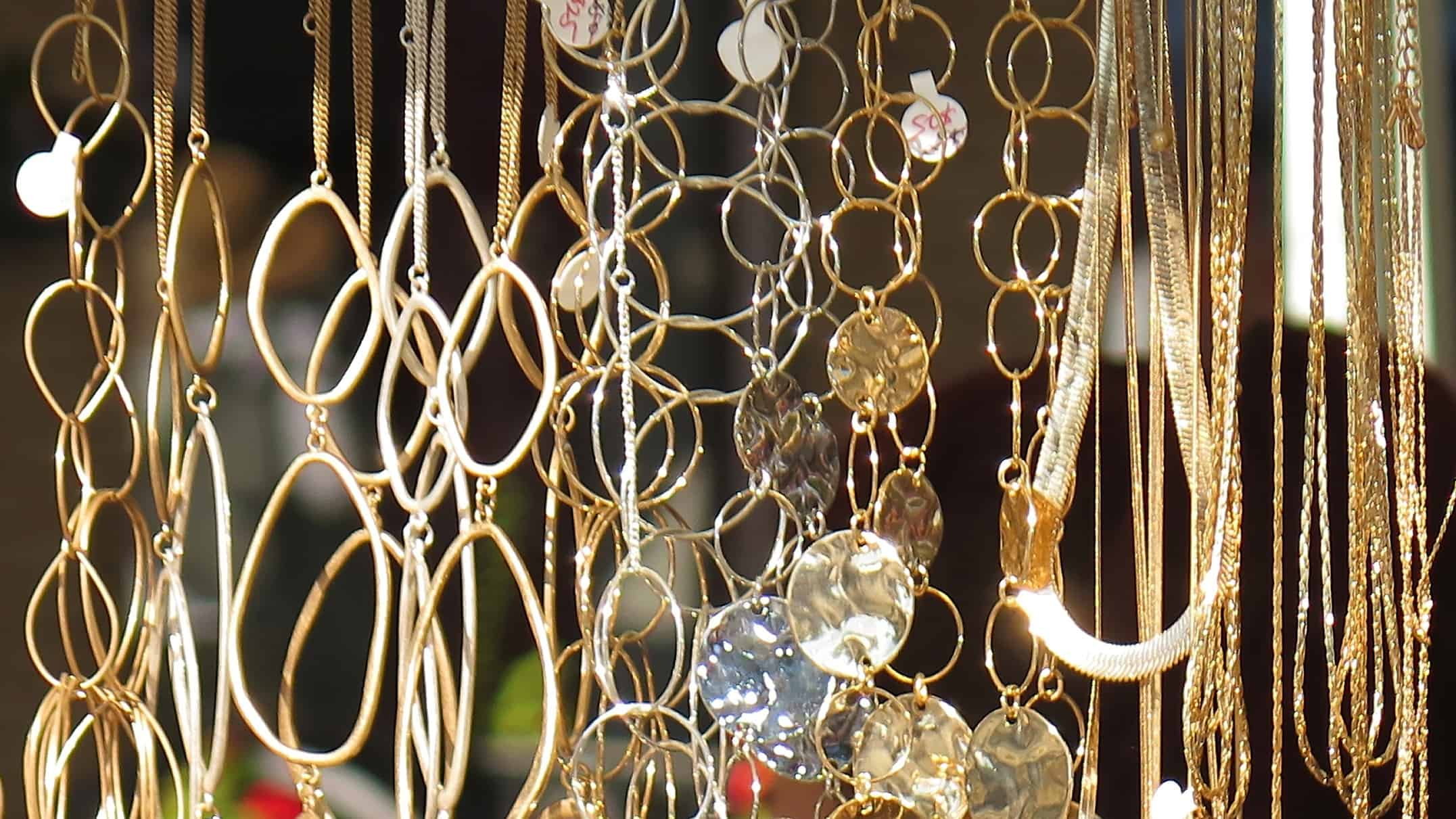 jewellery share price rise represented by lots of gold necklaces hanging in a row