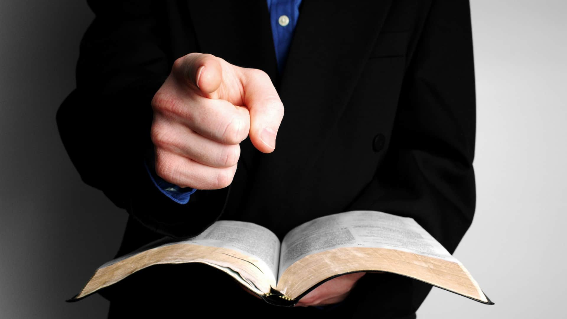 A man holds a law book and points his finger, indicating an accusation or alleged offence to be settled in court