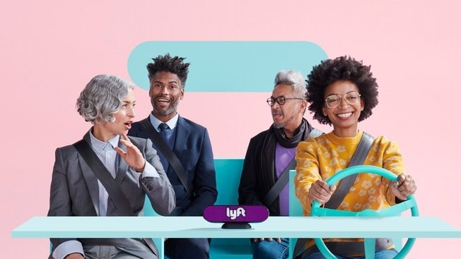 A group of four people riding a stylized car with lyft branding