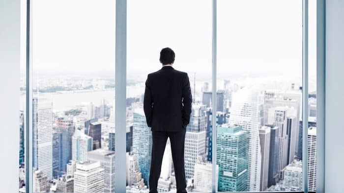 man looking through window at sky scraper buildings