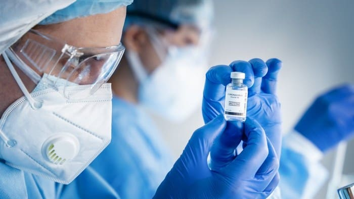 health professionals looking at a veil of moderna vaccine