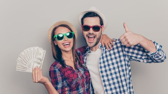 women and man holding money and happy
