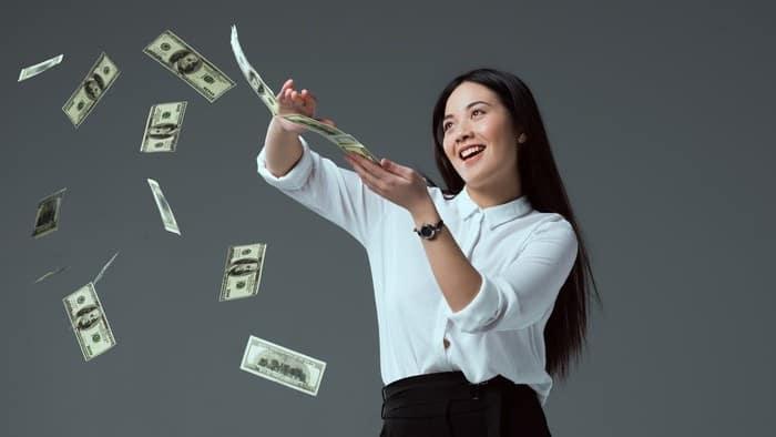 women splashing money in the air