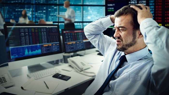 a trader on the stock exchange holds his head in his hands, indicating a share price drop