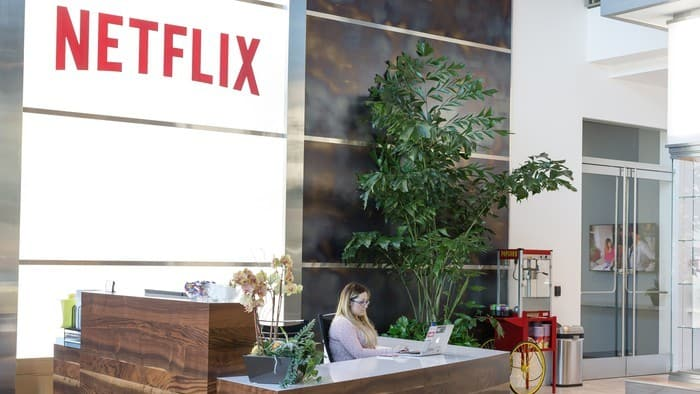 netflix stock represented by woman sitting behind reception desk at netflix office