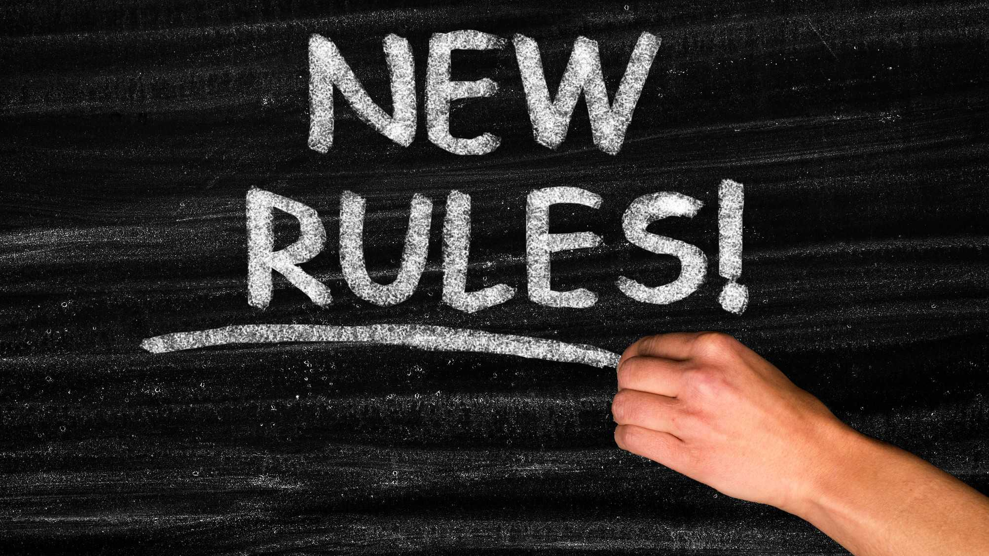 A chalkboard with hand wring the words New Rules, indicating regulation changes for an ASX share