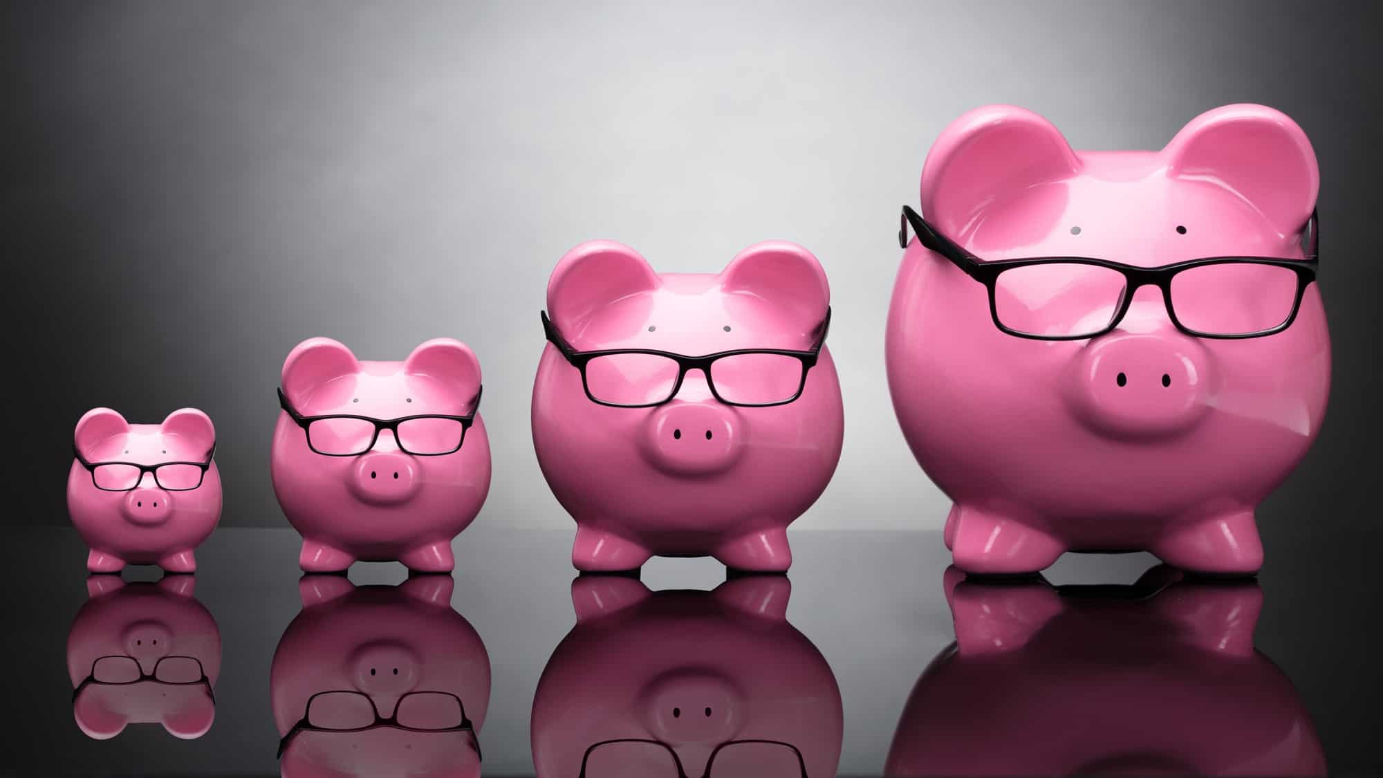 A row a pink piggy banks ranging in size from small to big, indicating ASX share price and dividends growth CBA bank dividend increase
