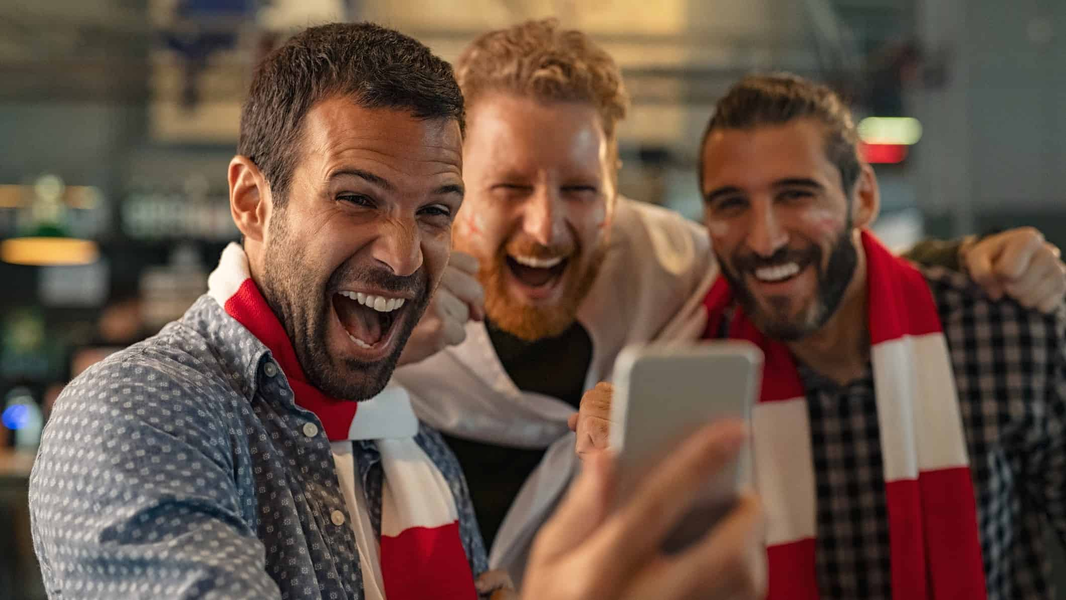 cheering sports fans looking at smart phone representing surging pointsbet share price