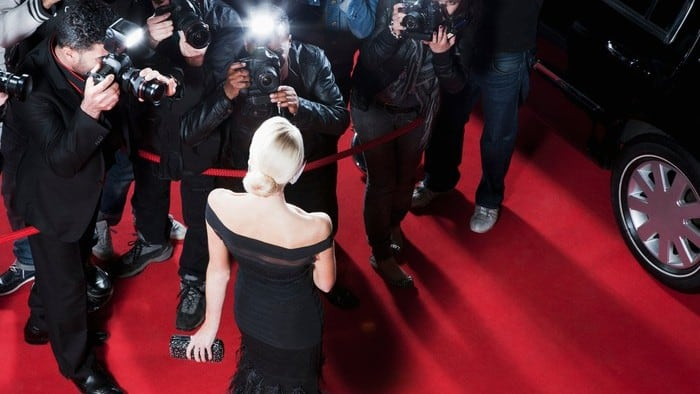 celebrity being photographed by the paparazzi on the red carpet