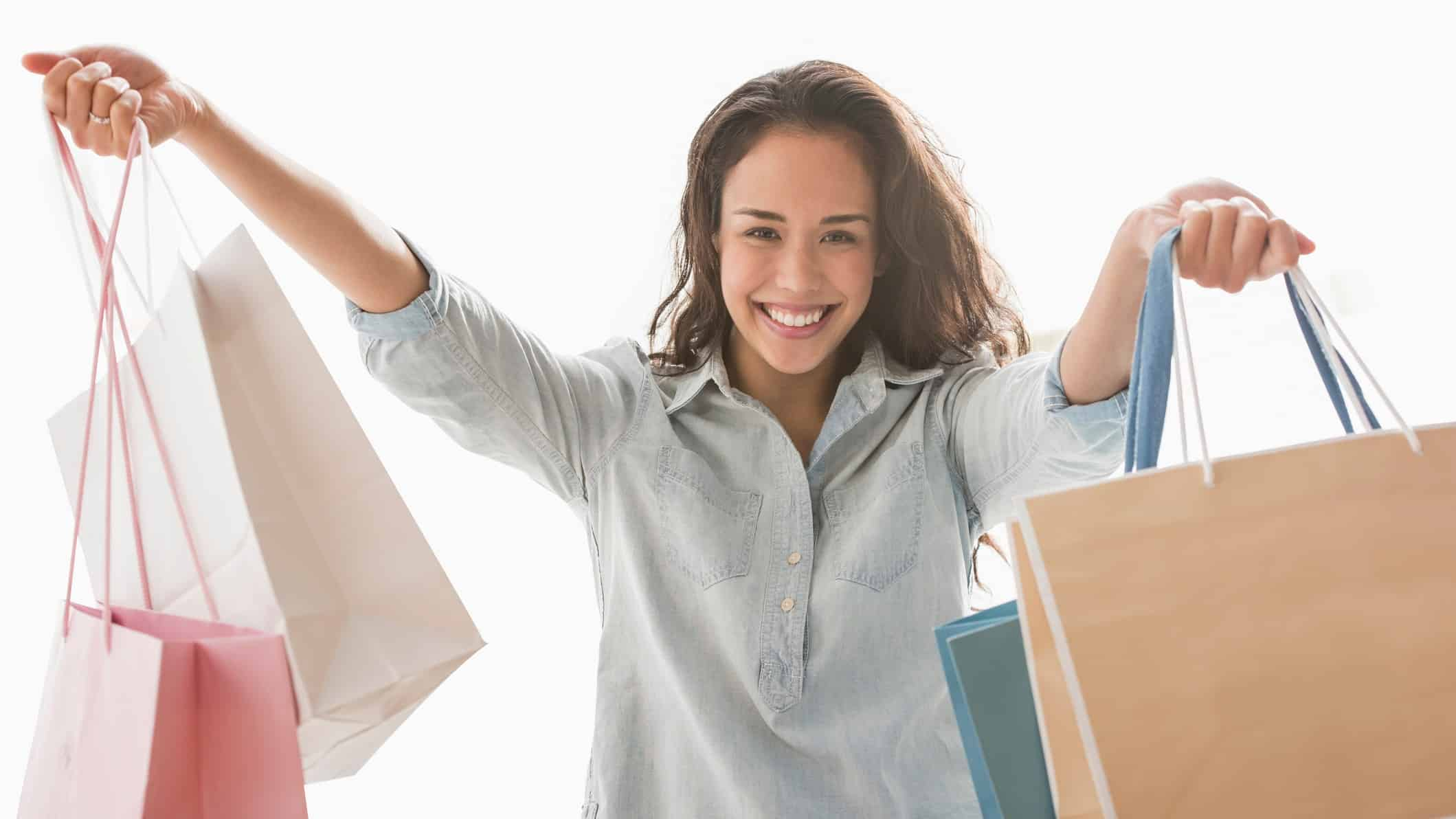 A happy shopper lifts her bags high, indicating a rising share price in ASX retail companies