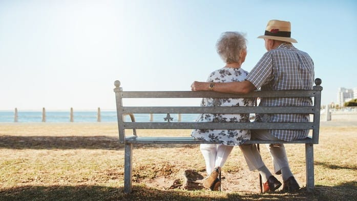 two retirees sitting on a bench together