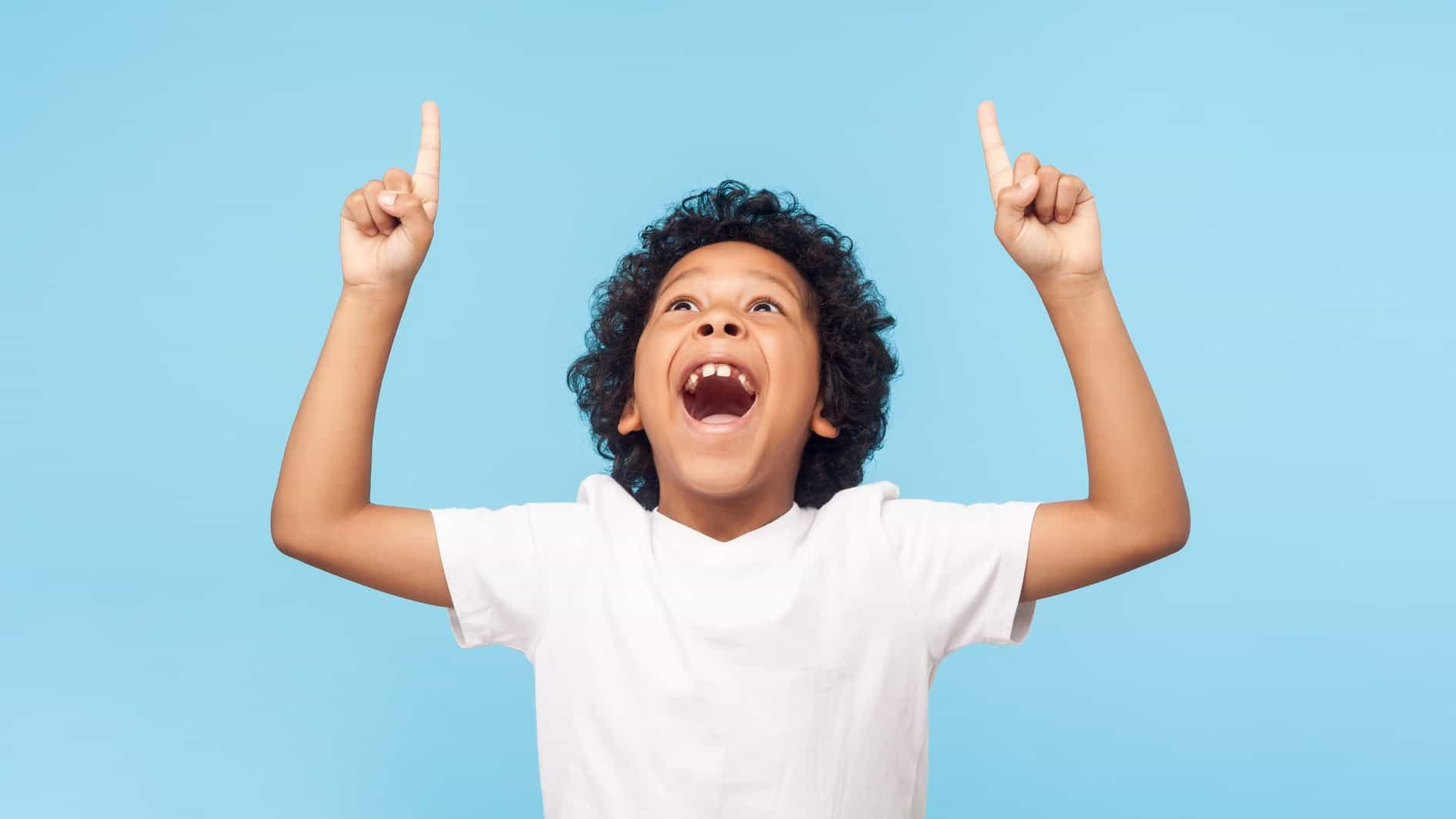 A happy smiling kid points his fingers up, indicating a rising share price
