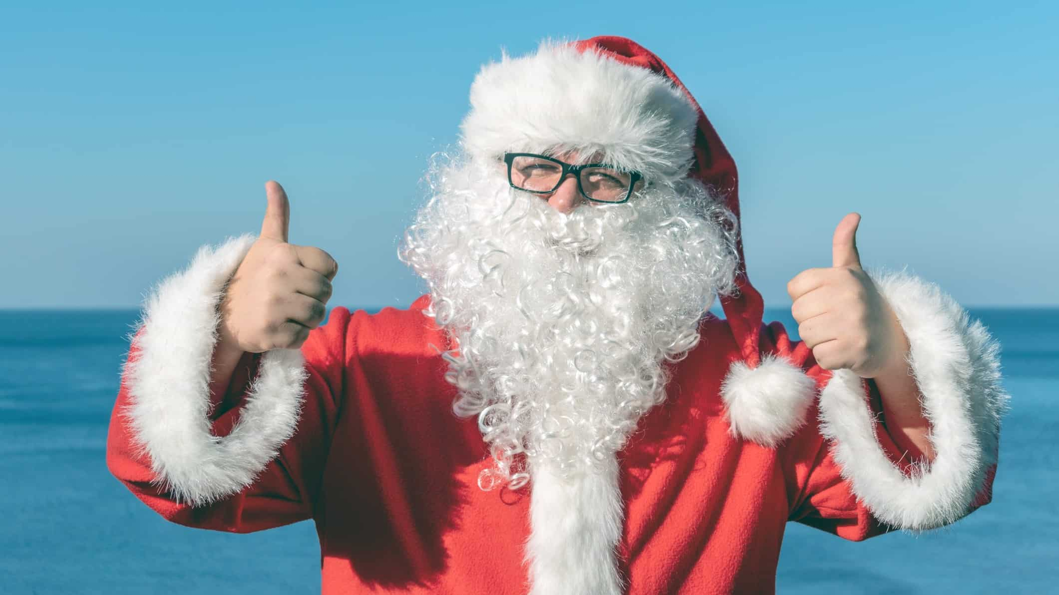 Santa at the beach gives a big thumbs up, indicating positive sentiment for the year ahead for ASX share prices