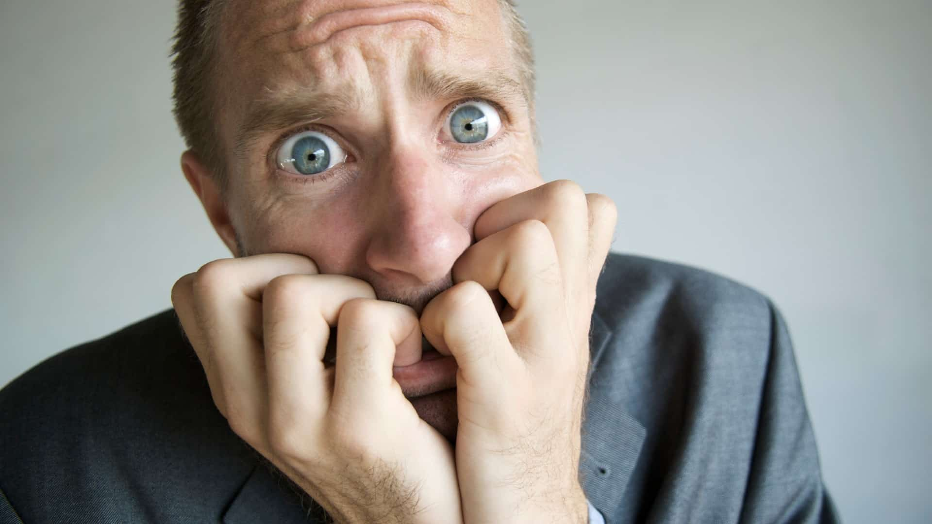 A worried man chews his fingers, indicating a share price crash or drop on the ASX