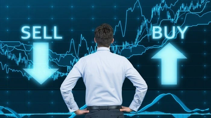 A trader stand looking at a sharemarket graph emblazoned with the words buy and sell