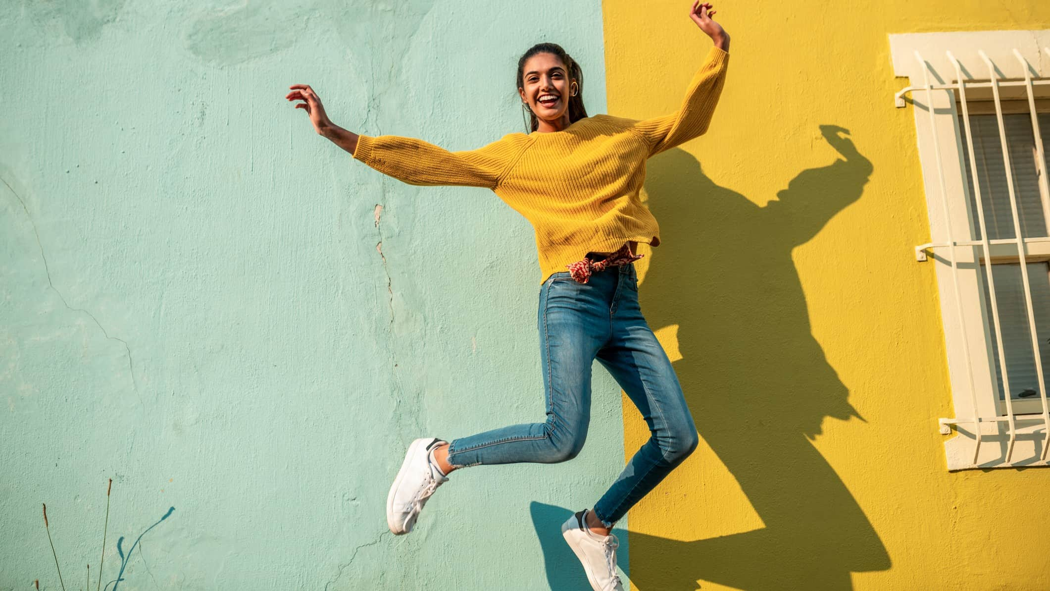 rising asx share price represented by woman jumping in the air happily