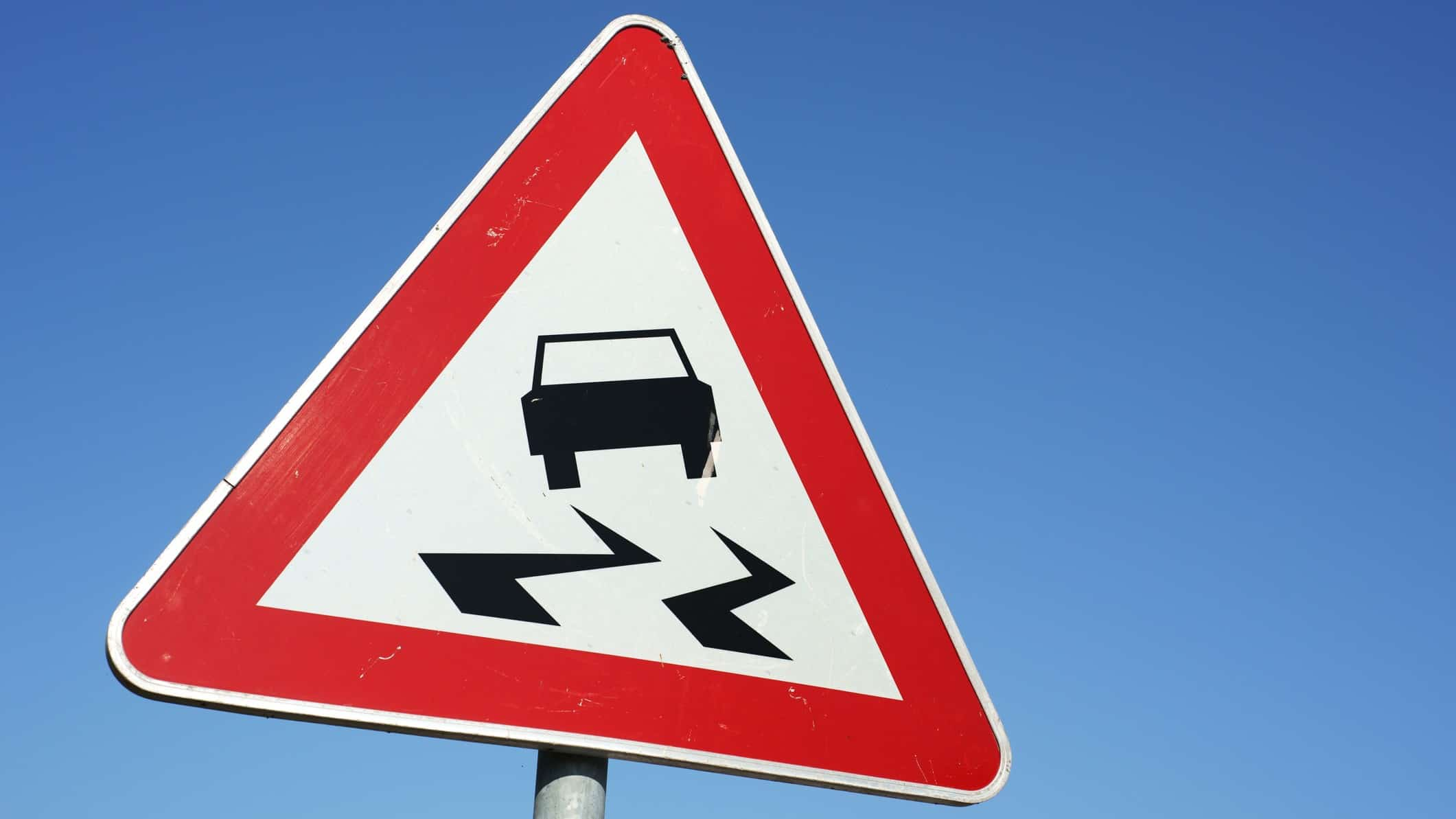 ASX share price slide represented by urban street sign with car sliding
