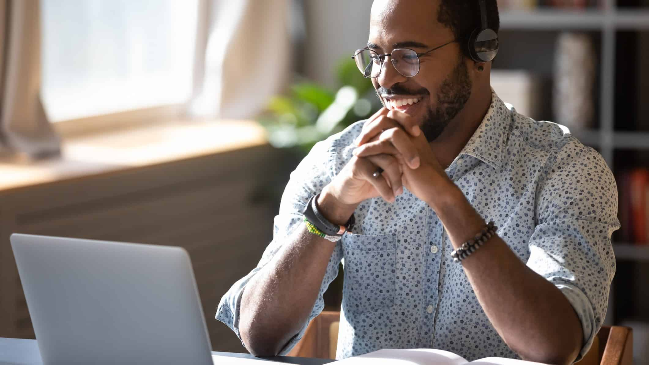 Young male investor smiling looking at laptop