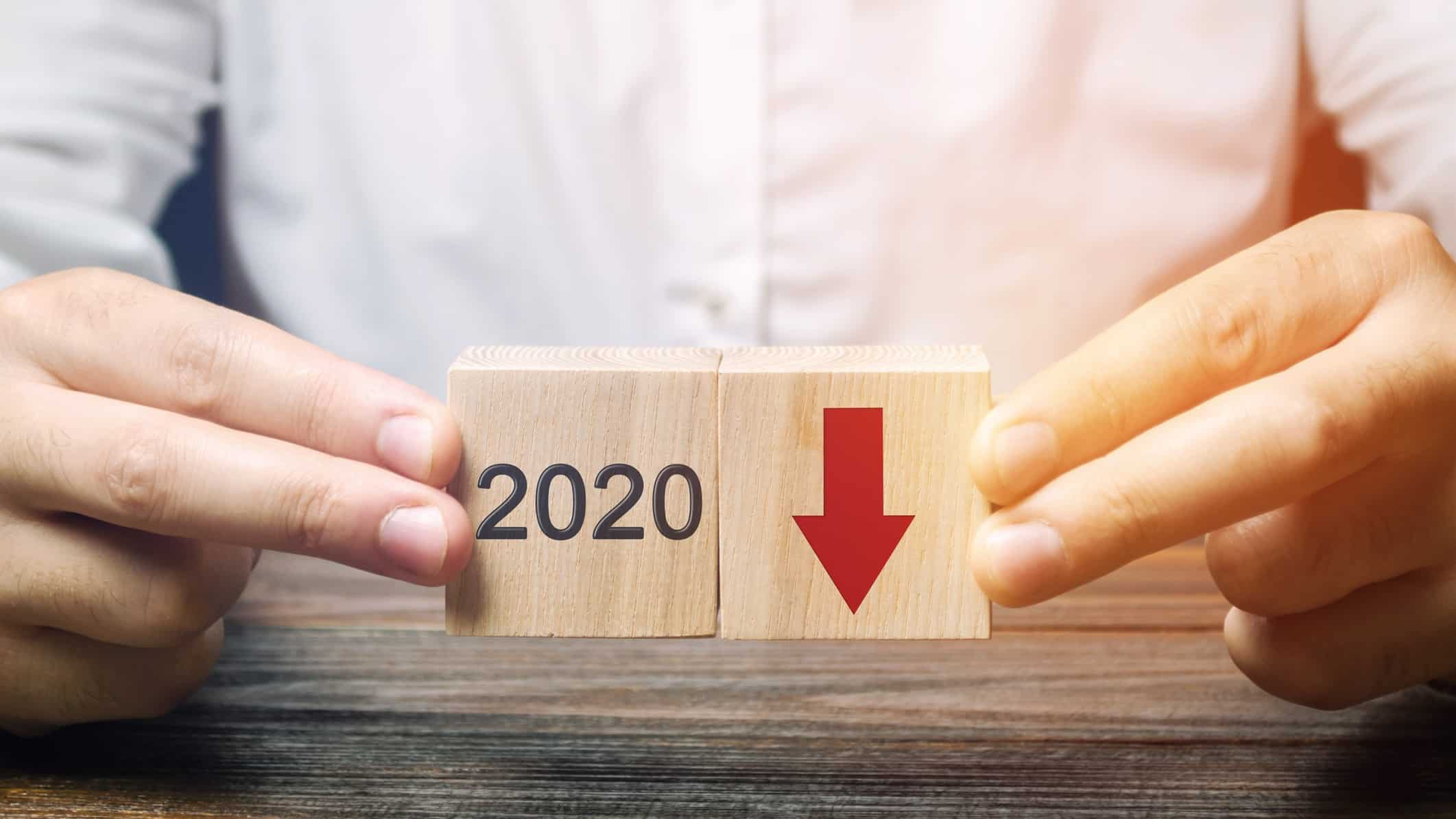 man holding wooden blocks with red down arrow and 2020 on them representing falling South32 share price
