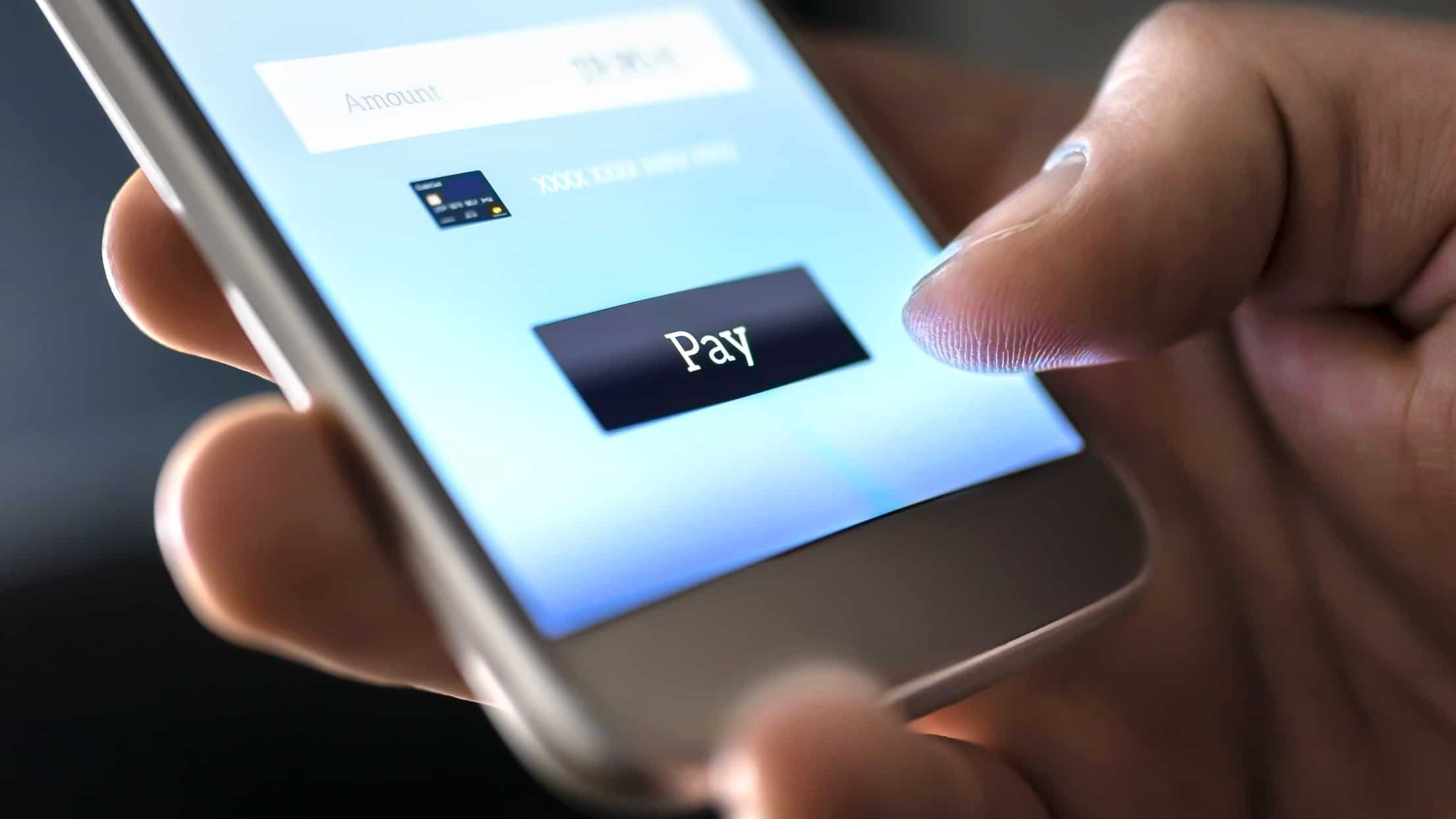 hand holding mobile phone about to make credit card payment