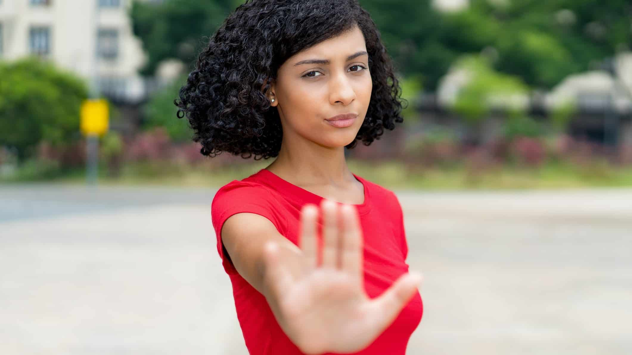 A serious woman put her hand out indicating stop