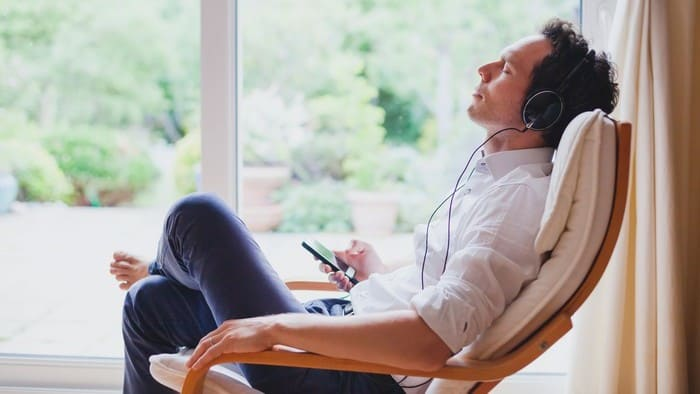 streaming stock represented by man relaxing in chair listening to music