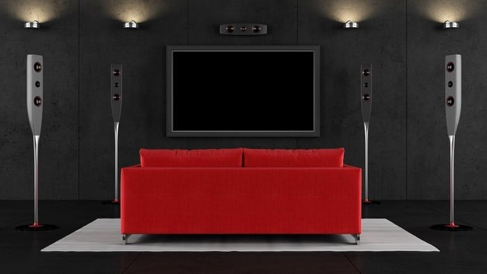 streaming shares represented by large tv on wall in front of red couch