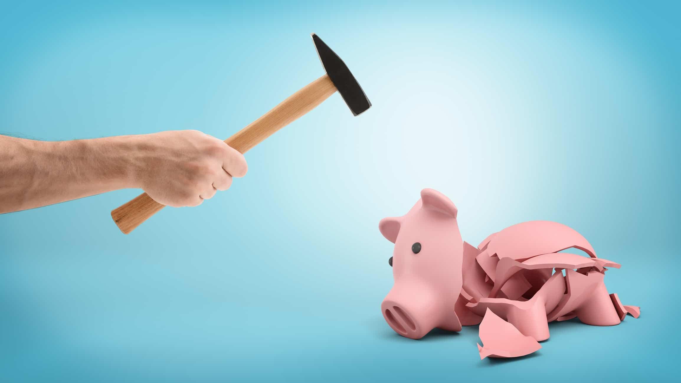 hand holding hammer smashing open empty piggy bank