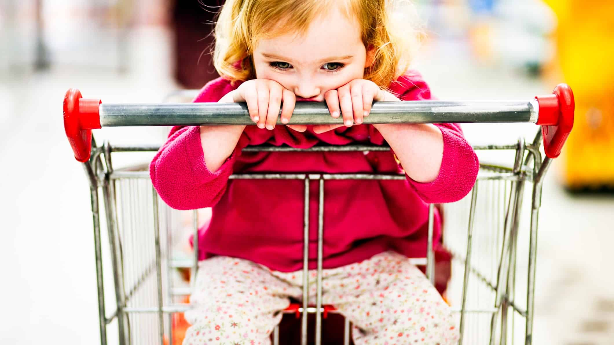 A sad little girl sits in a supermarket trolley, indicating a decline in share market price