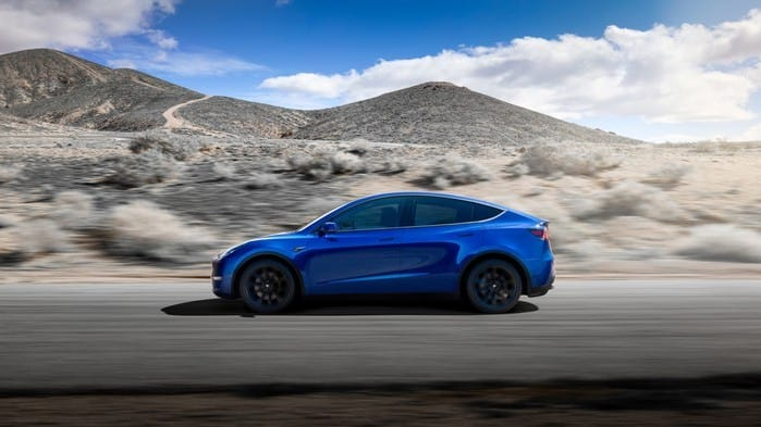 tesla stock represented by person driving blue tesla car