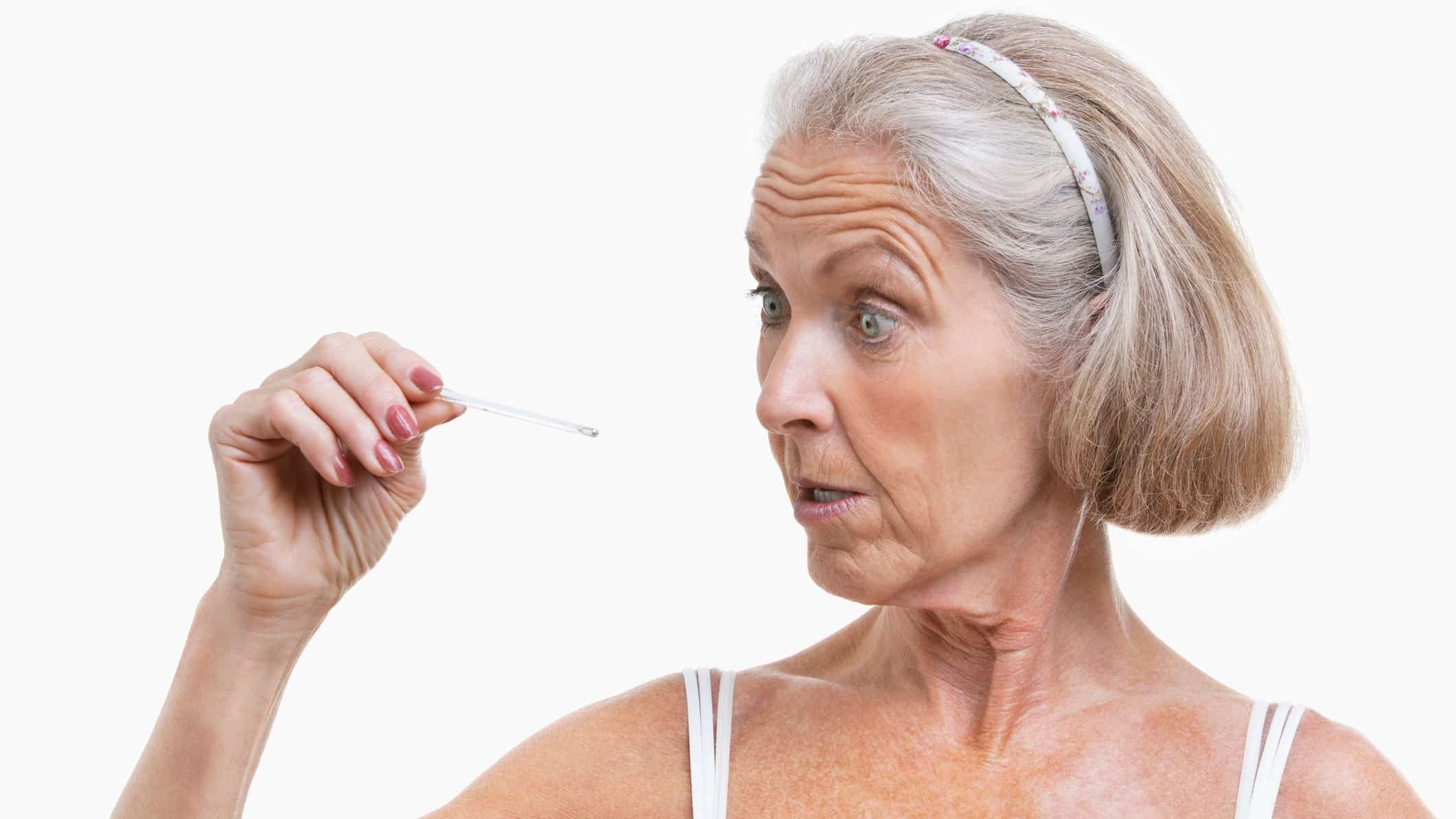 A woman looks surprised as she checks an old-fashion thermometer, indicating a change in share price moevement for biotech companies
