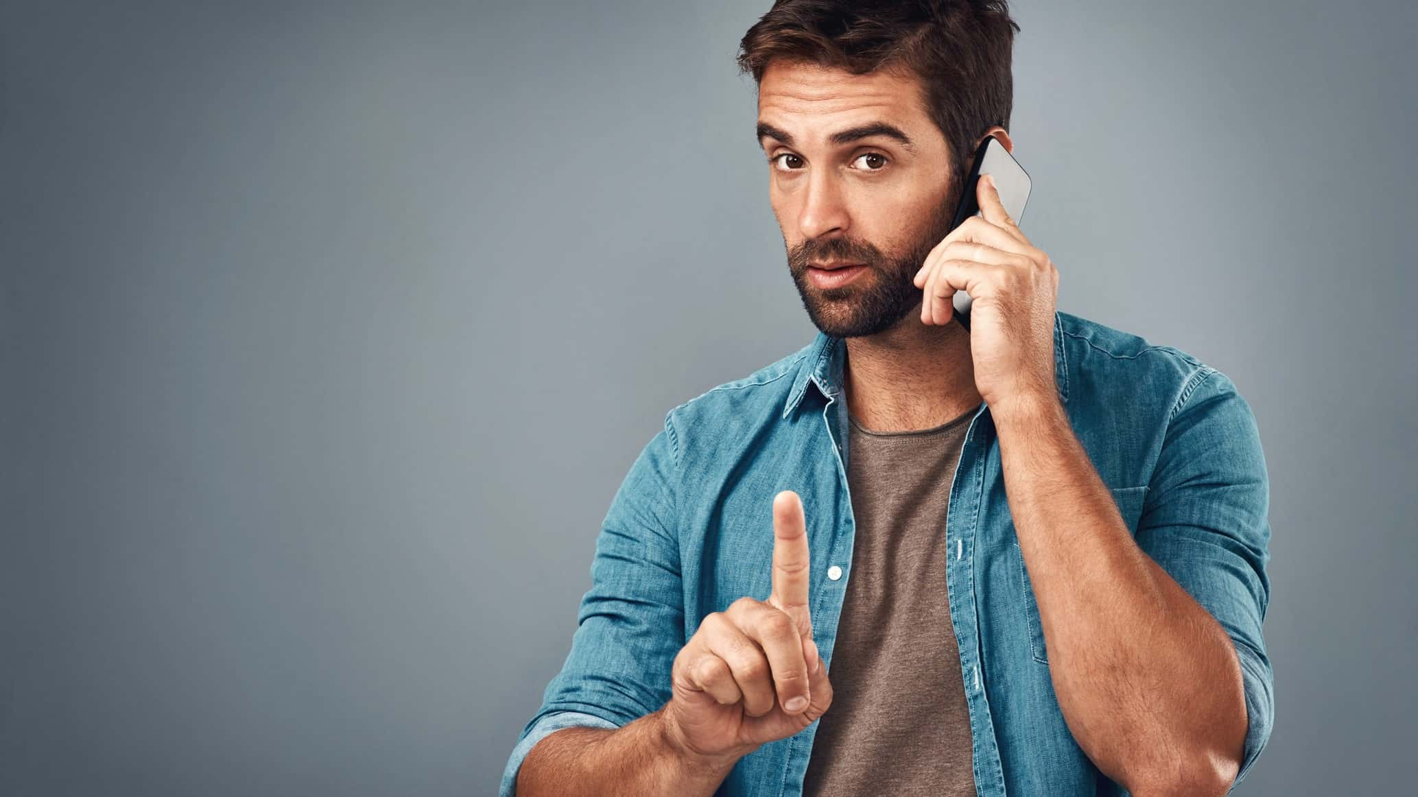 A man on a phone call points his finger, indicating a halt in trading on the ASX share market