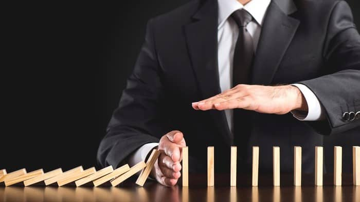 asx share price in trading halt represented by business man stopping falling row of dominoes