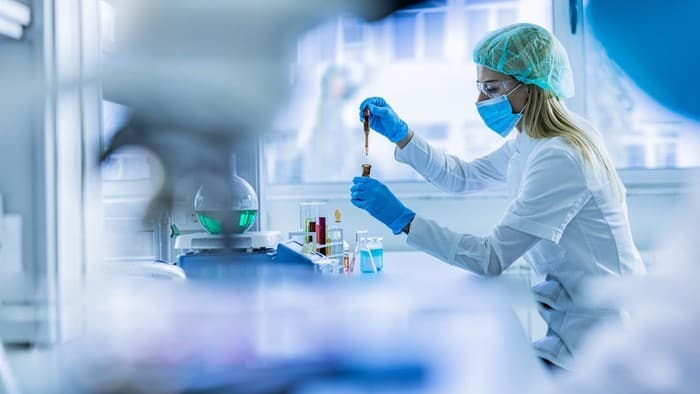 asx share associated with COVID vaccine represented by lab tech drawing down syringe