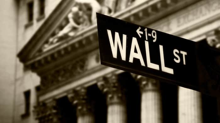wall st sign with a building in the background