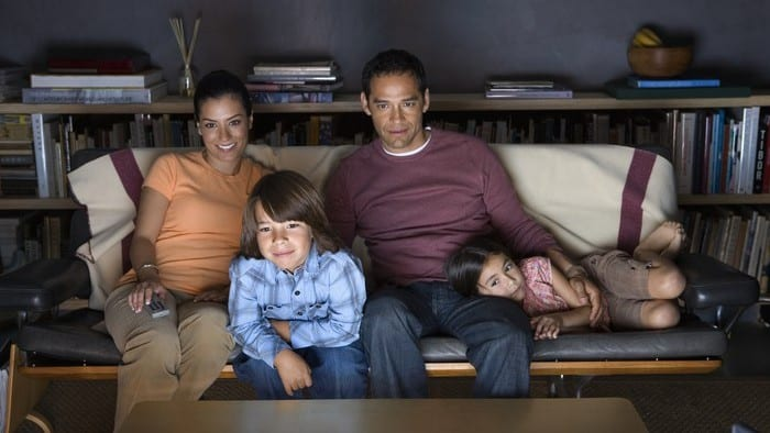 Family of four sitting on couch watching Netflix