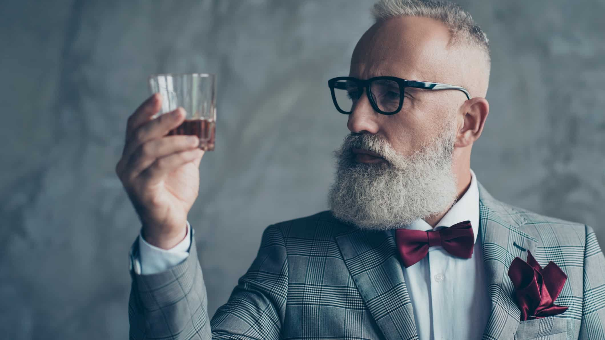 A hipster man holds up a glass of whiskey, indicating a share price watch for ASX wine and gin producers