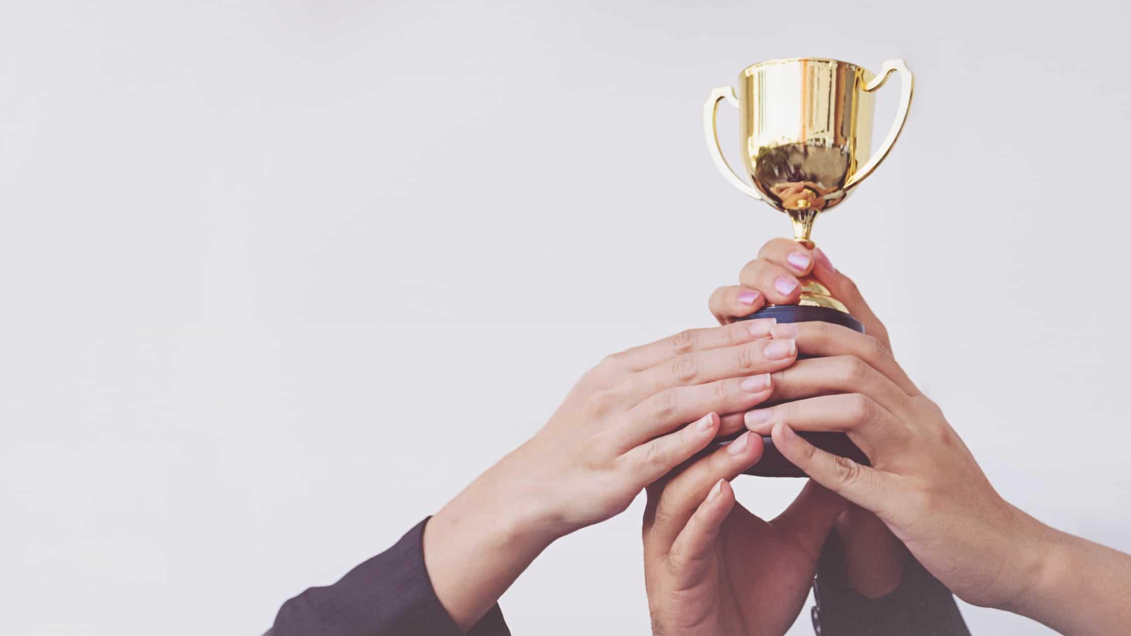 hands holding up winners cup, asx 200 winning shares