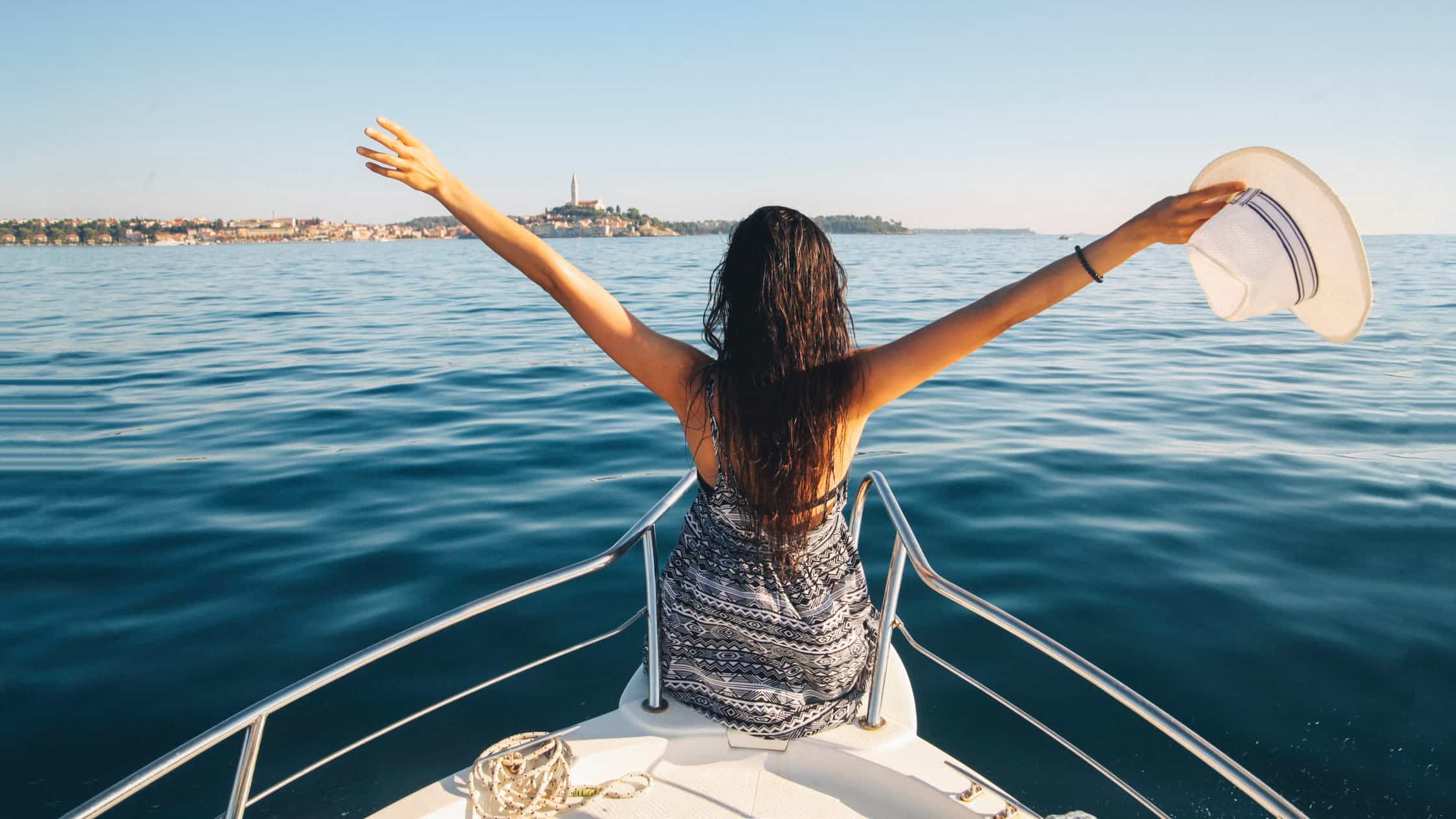 A young woman sitting atop a superyacht spreads her arms in joy, indictaing a share price rise for marine companies